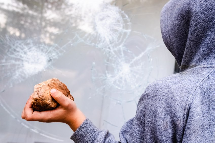 person holding rock near broken window